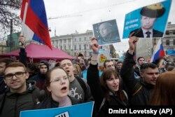 Демонстранти несуть плакати із зображенням російського президента Володимира Путіна під час масового акції протесту в Санкт-Петербурзі, 5 травня 2018 року. Підпис на плакаті говорить: «Він не є для нас царем»