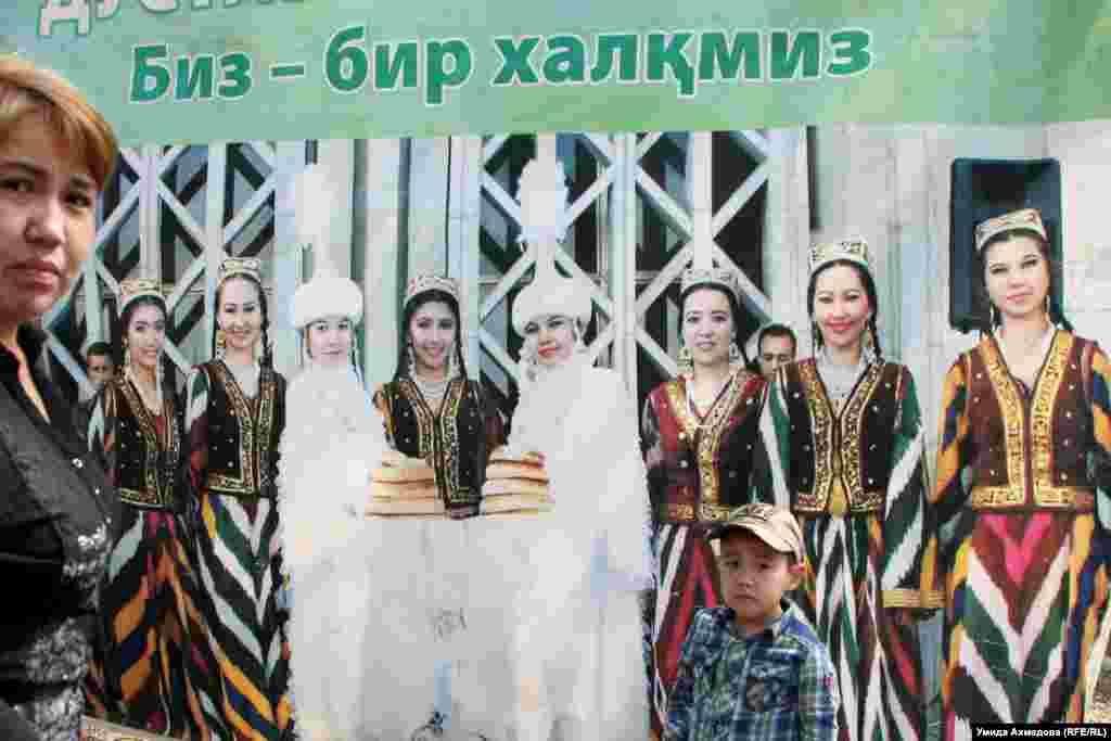 Қазақ және өзбек ұлттық костюмдерін киген қыздар суретінің жанында тұрған әйел мен бала.