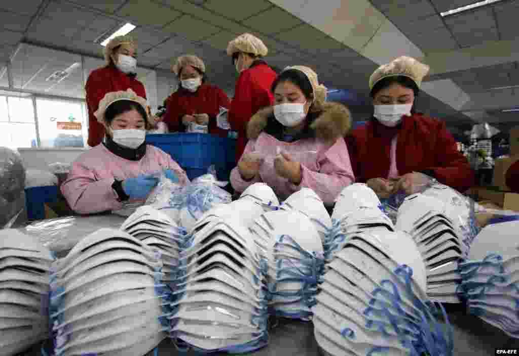Медициналық маска шығаратын зауыт жұмысшылары. Қытайда вирус тарағаннан кейін маскаға сұраныс күрт артқан. Ханьдань, Хэбэй провинциясы. 23 қаңтар 2020 жыл.