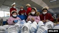Работники завода, производящего защитные маски для лица. Маски в дефиците из-за вспышки коронавируса. Ханьдань, провинция Хэбэй. 23 января 2020 года.