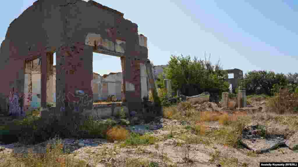 Рядом на берегу – то, что осталось от заводского корпуса