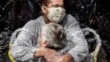Rosu Luziju Lunardi (85) grli medicinska sestra Adriana Silva da Costa Souza u domu za njegu starijih osoba Viva Bem, Sao Paulo, Brazil, 5. august 2020.<br /> <br /> Ovo je bio prvi zagrljaj koji je Rosa primila u posljednjih pet mjeseci. U martu su domovi za njegu širom zemlje zatvorili vrata za sve posjetioce kao rezultat pandemije COVID-a 19, što je spriječilo milione Brazilaca da posjete stariju rodbinu.<br /> <br /> Njegovateljima je naređeno da fizički kontakt sa ranjivim osobama svedu na apsolutni minimum. Jednostavni izum, &quot;Zagrljaj zavjesa&quot;, u Viva Bemu omogućio je ljudima da se zagrle.<br /> <br /> Kategorija World Press Photo Story of the Year: Pobjednik - Mads Nissen, Politiken / Panos Pictures