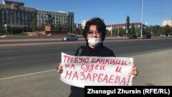 Правозащитница Алима Абдирова держит плакат с призывом ввести санкции в отношении судей и бывшего президента Казахстана Нурсултана Назарбаева. Актобе, 16 сентября 2021 года