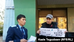 Активист Макс Бокаев (справа) проводит пикет в поддержку активистов Серикжана Мамбеталина и Ермека Нарымбаева перед зданием суда. Алматы, 26 октября 2015 года.