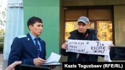 Активист Макс Бокаев (справа) проводит пикет в поддержку активистов Серикжана Мамбеталина и Ермека Нарымбаева перед зданием суда в Алматы. Представитель прокуратуры сообщает Бокаеву об отсутствии санкции на протест. 26 октября 2015 года.