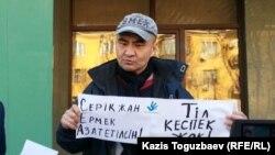 Активист Макс Бокаев проводит пикет в поддержку арестованных активистов Серикжана Мамбеталина и Ермека Нарымбаева перед зданием суда Алматы. 26 октября 2015 года.