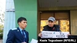 """Гражданский активист Макс Бокаев (справа) проводит пикет в поддержку активистов Серикжана Мамбеталина и Ермека Нарымбаева, арестованных по обвинению в """"разжигании розни"""". Алматы, 26 октября 2015 года."""