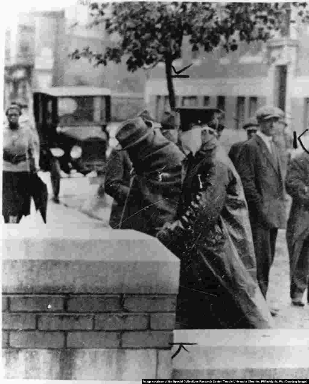 Полицейский сопровождает больного «испанкой» в больницу в Филадельфии в октябре 1918 года.