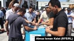 Борбордук мечиттин алдындагы үкөккө битир-садака таштап жаткандар. Бишкеке, 17-август, 2012.