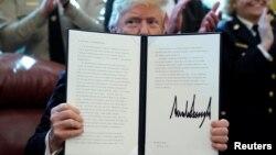 Дональд Трамп демонстрирует подписанный им указ (архивное фото, 15 марта 2019)