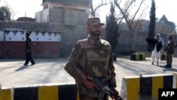 An army soldier stands near the World Food Program distribution point hit by a female suicide bomber in Khar, Pakistan.
