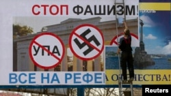 Ukraine -- A man pastes another poster over one calling for people to vote against fascism in an upcoming referendum in the Crimean port city of Sevastopol, March 10, 2014