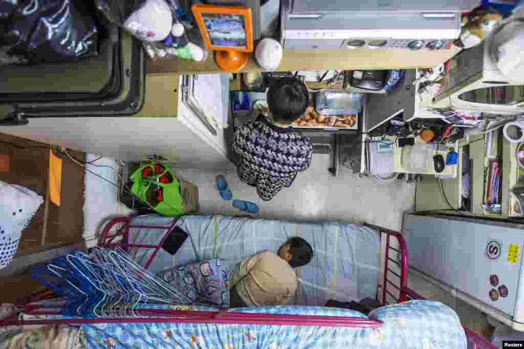 A woman and her son in their 5.6-square-meter subdivided flat in Hong Kong, which has a monthly rent of $487