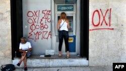 Жінка знімає грощі з банкомату поруч з написом «ні» (OXI) на стіні. Салоніки, 6 липня 2015 року