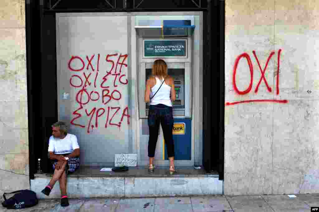 "A woman withdraws money from an ATM machine next to a beggar and graffiti reading ""No To Fear"" in Thessaloniki, Greece. (AFP/Sakis Mitrolidis)"
