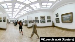 A gold-painted art lover who was wearing only a red thong strolled through the Tretyakov Gallery in Moscow on March 20.