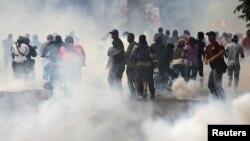 Сторонники лидера оппозиции Энрике Каприлеса, требующие пересчета голосов после выборов, отступают перед слезоточивым газом, 15 апреля 2013