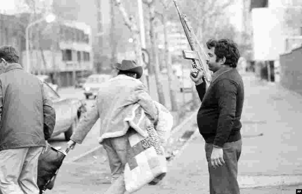 A U.S.citizen carries belongings past an armed Khomeini loyalist who is guarding an evacuee staging area in Tehran on February 17, 1979. Hundreds of Americans began to flee Iran following the first attempt to seize the U.S. Embassy.