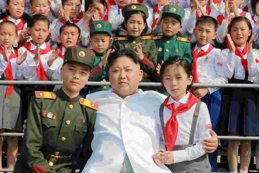 Schoolchildren stand beside North Korean leader Kim Jong Un as he arrives to attend We Are The Happiest In The World, a performance of schoolchildren to celebrate the 70th founding anniversary of the Korean Children's Union in Pyongyang. (Reuters/KCNA)