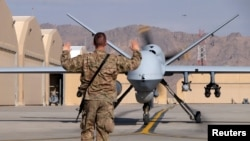 A U.S. airman guides a US Air Force MQ-9 Reaper drone as it taxis to the runway at Kandahar airfield in March.