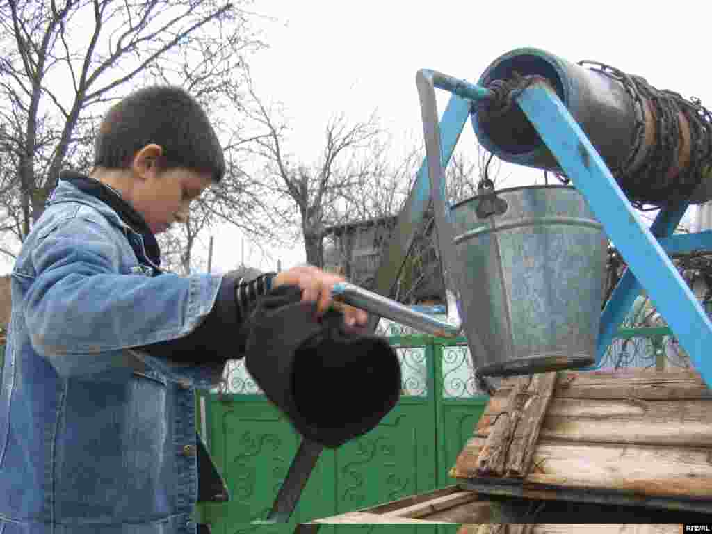 Vasilica Bejan draws water from a well. While life is hard at home, he's happier there than in the orphanage.