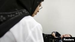 Иранская женщина-врач взвешивает грудного ребенка. Иллюстративное фото.