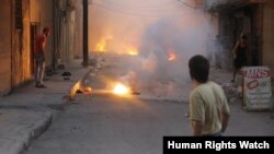 Dy njerëz duke e shikuar zjarrin nga të shtënat në Alepo të Sirisë