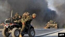 یک سرباز گرجستانی به دلیل شلیک راکت به مسیر یک کاروان نظامی وسیله نقلیه خود را ترک می کند.(عکس: AFP)