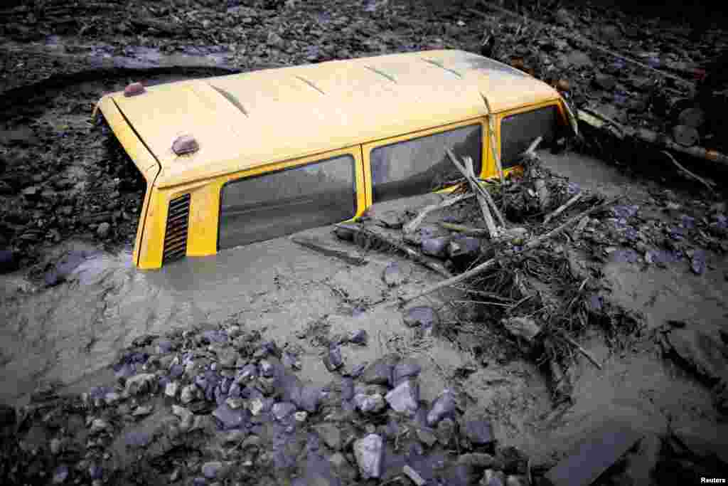 A vehicle is buried in mud in Topcic Polje, Bosnia-Herzegovina.