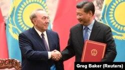 Қазақстан президенті Нұрсұлтан Назарбаев пен Қытай төрағасы Си Цзиньпин құжаттарға қол қою рәсімінде қол алысып тұр. Пекин, 7 маусым 2018 жыл.
