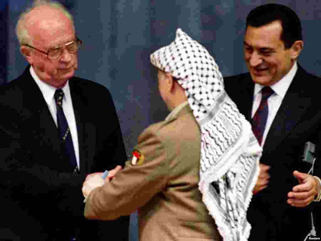 Mubarak looks on as Israel's Prime Minister Yitzhak Rabin (left) shakes hands with PLO Chairman Yasser Arafat. - Mubarak hosted the historic signing ceremony as Arafat signed the PLO-Israeli peace accords on limited Palestinian self-rule for the Gaza Strip and Jericho in Egypt on May 4, 1994.