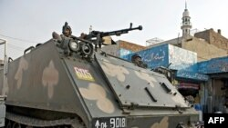 An armored personnel carrier patrols along a street in Lahore.