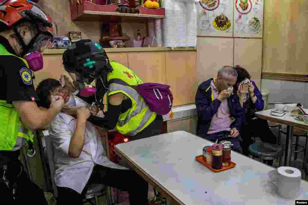 Работнику одного из ресторанов оказывают помощь волонтеры, посетители прикрывают носы и рты после того, как спецназ распылил неподалеку слезоточивый газ для разгона протестующих, Гонконг, 2 ноября 2019 года.