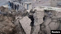 Afghan villagers gather at the site of a landslide in the Argo district of Badakhshan Province on May 2.