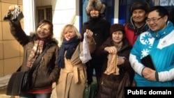 Задержанные во время митинга против девальвации (слева направо в первом ряду) Жанна Байтелова, Евгения Плахина и Валерия Ибраева показывают трусы у здания суда, где им присудили штрафы. Алматы, 16 февраля 2014 года.