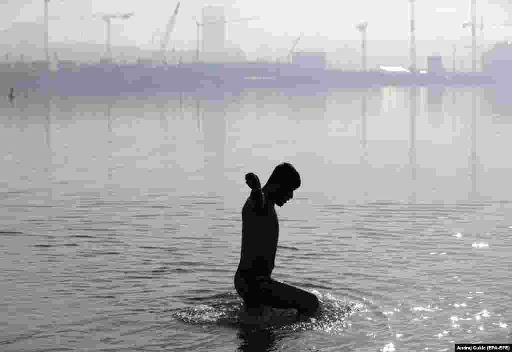 A migrant from Afghanistan bathes in the Sava River in Belgrade, Serbia. (epa-EFE/Andrej Cukic)