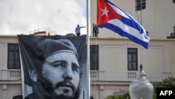 A Cuban flag flutters at half-staff near a banner depicting Cuban revolutionary leader Fidel Castro, two days after his death, in Havana on November 27.