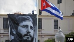 CUBA -- A Cuban flag flutters at half mast near a banner depicting Cuban revolutionary leader Fidel Castro, two days after his death, in Havana on November 27, 2016.