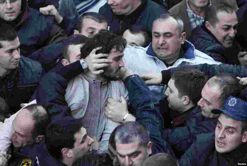 Protesters scuffle outside the National Library in the Georgian capital, Tbilisi. Hundreds of protesters gathered in an attempt to block President Mikheil Saakashvili from entering the building to deliver his last annual address to the nation. (Reuters/David Mdzinarishvili)