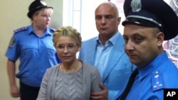 Yulia Tymoshenko inside the court hearing room with her husband, Oleksandr, in Kyiv on August 11.