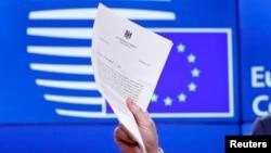 Președintele Consiliului European Donald Tusk arată jurnalștilor scrisoarea semnată de premierul britanic Theresa May.
