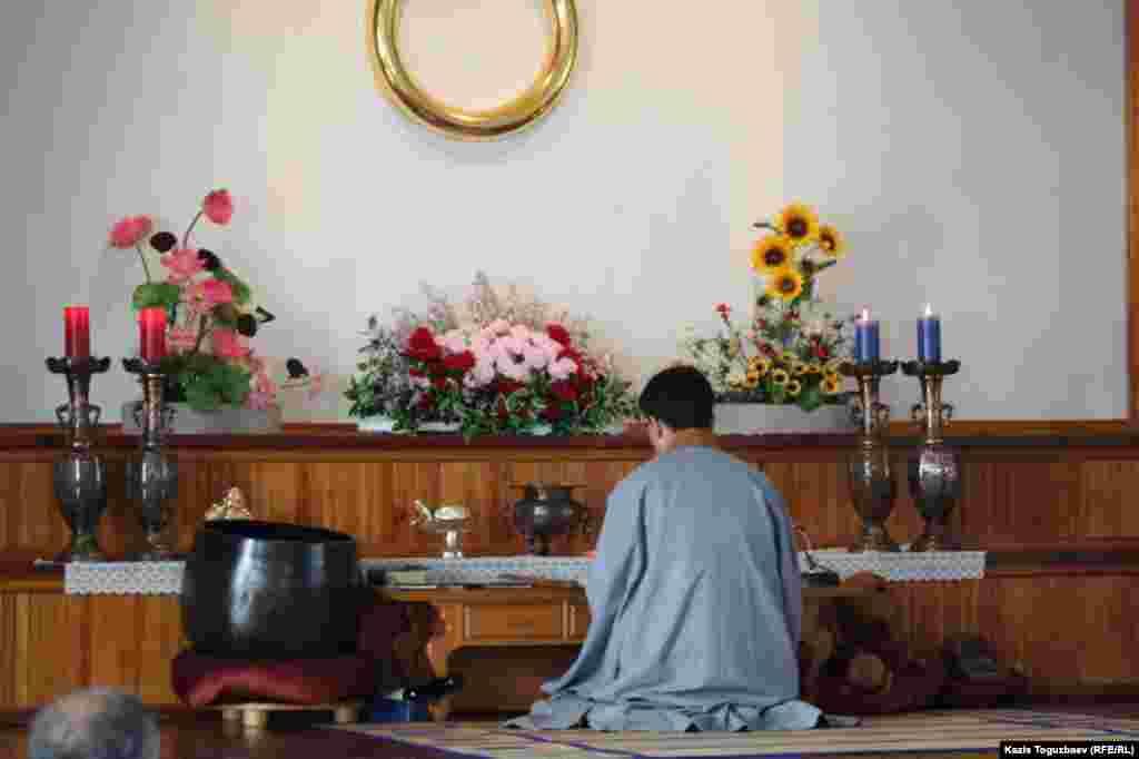 Проповедник алматинской буддистской организации Ким Тэ Иль у алтаря во время богослужения.