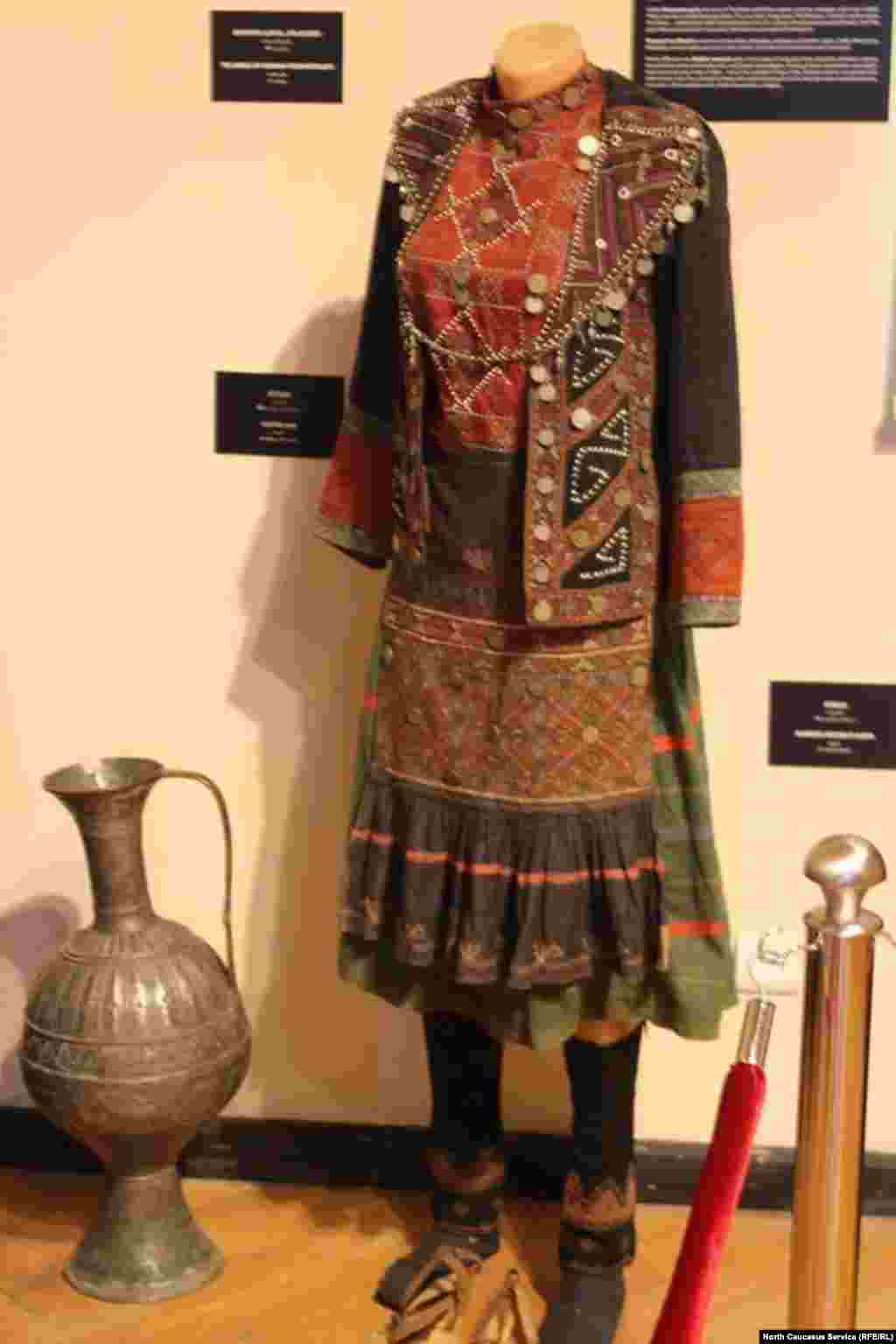Платье вышито национальным орнаментом и украшено монетами.