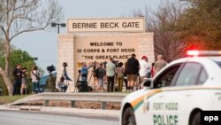 News media gather outside one of the entrances to the Fort Hood military base near Killeen, Texas, on April 2.