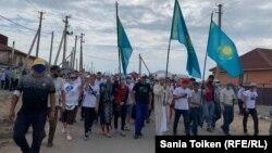 Прибывшие в село Талапкер люди идут к кладбищу, где похоронен Дулат Агадил. Акмолинская область, 4 августа 2020 года.
