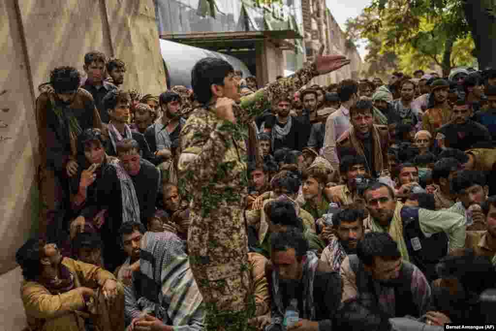 Афганцы чакаюць перад банкам, спрабуючы зьняць грошы. Кабул