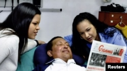 Venezuelan President Hugo Chavez holds a copy of the newspapers with his daughters Rosa Virginia (right) and Maria while recovering from cancer surgery in Havana.
