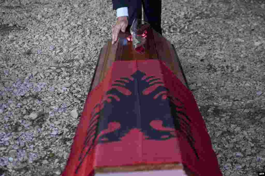 An ethnic Albanian man touches a coffin during a handover ceremony of mortal remains of 12 Kosovar Albanians during a ceremony in the village of Merdare. The remains were found at a mass grave in Serbia, identified 15 years after the war, and will be handed over to the families. (AFP/Armend Nimani)
