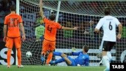 Нидерланд қақпашысы Мартен Стекеленбургтің (көк киімде) допты ұстай алмай қалған сәті. Украина, Харьков, 13 маусым 2012 жыл.