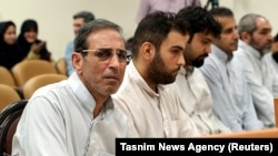 Vahid Mazloumin (left) appears in court in Tehran on charges of manipulating the currency market on September 8.